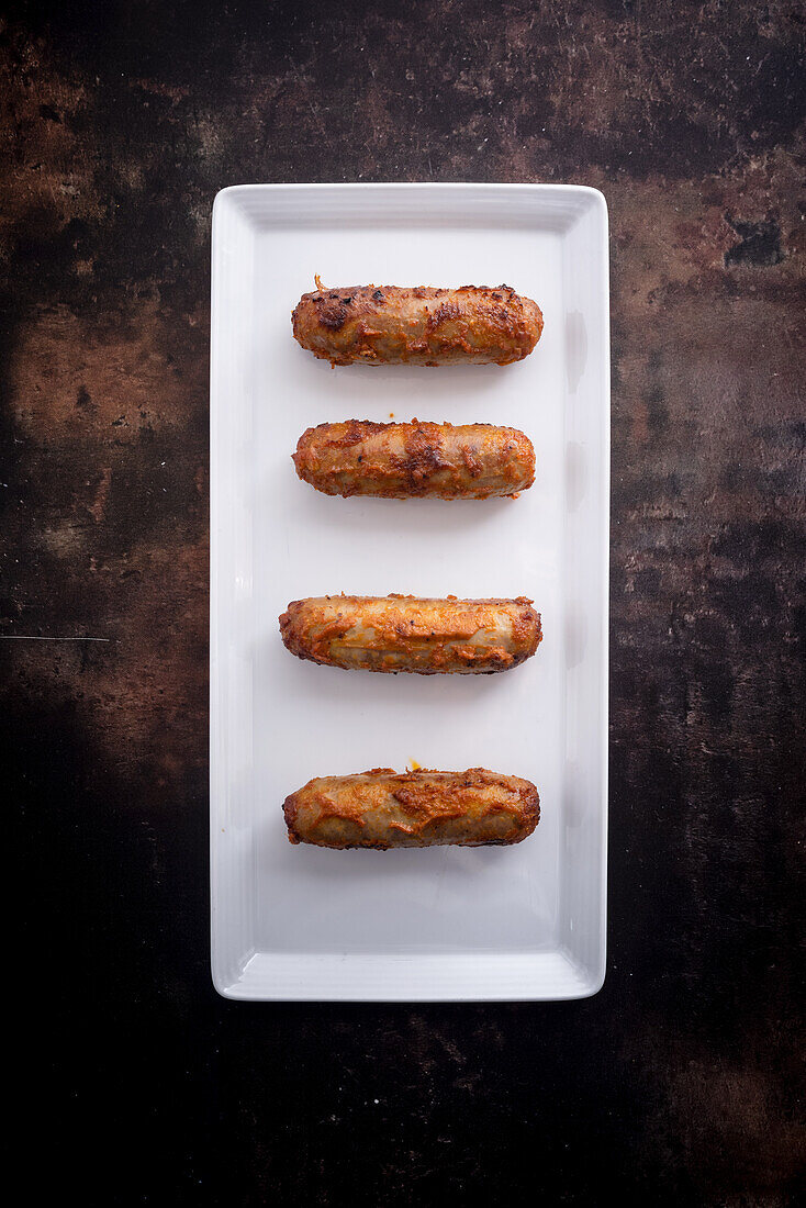 Fried duck sausages (India) on a serving platter against a dark background