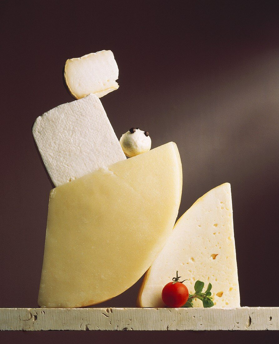 Still life with various types of cheese, cherry tomato,marjoram