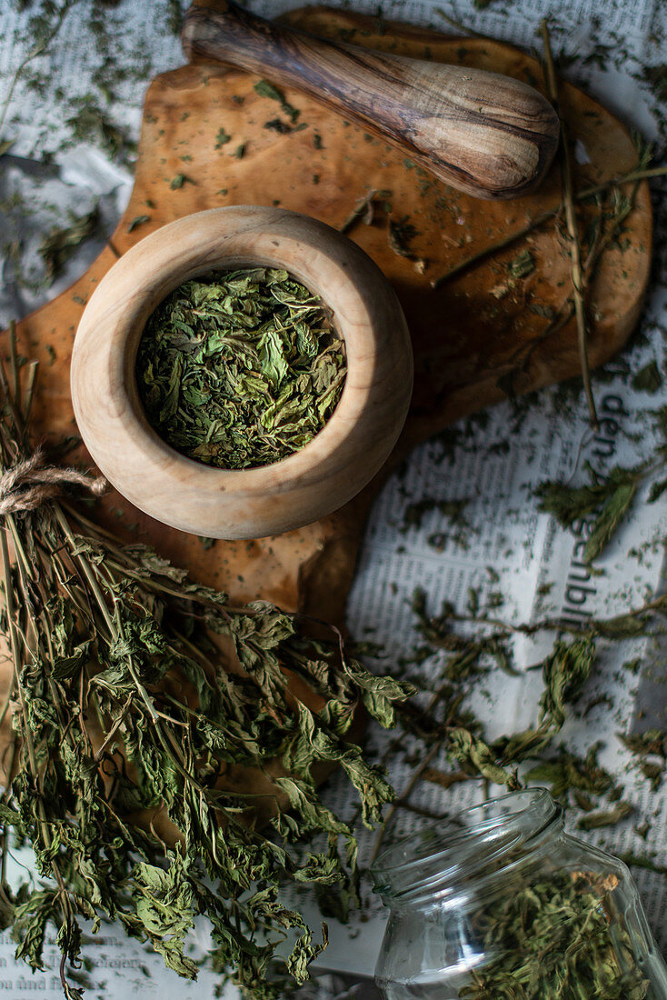 Dried mint on a wooden surface and in a wooden mortar