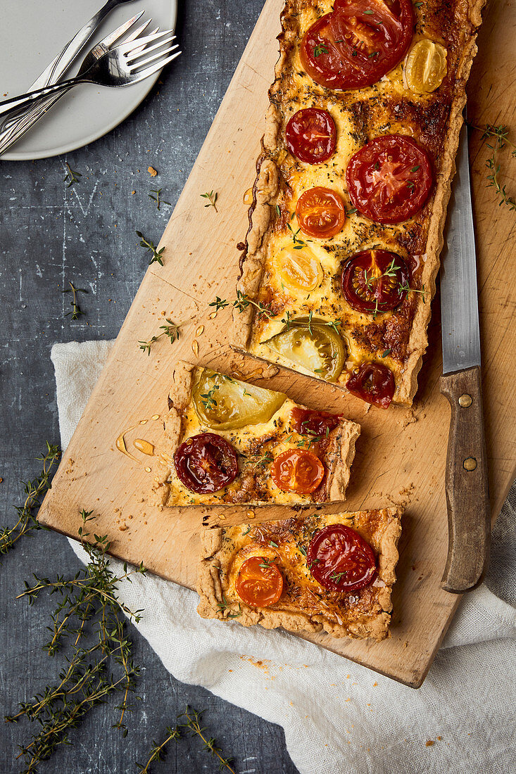 A colourful tomato quiche with thyme, sliced