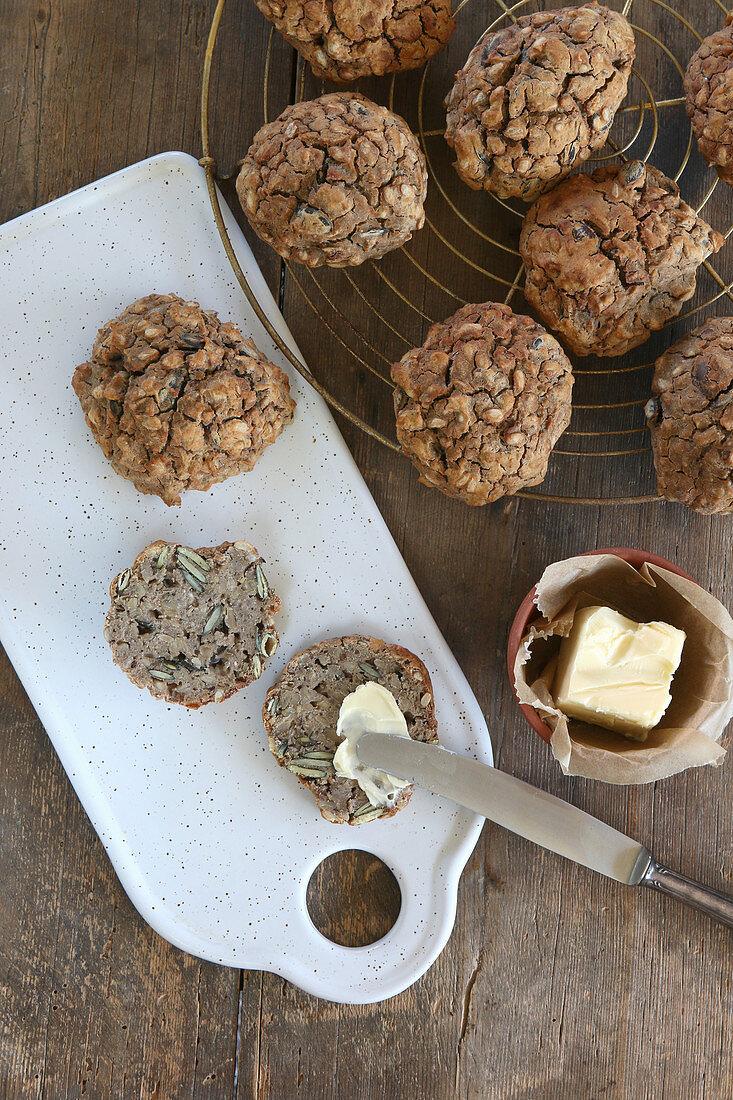 Homemade gluten-free oat and pumpkin seed rolls with butter