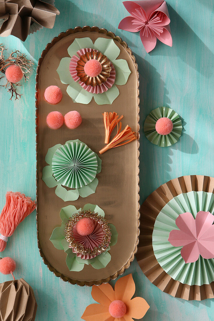 Homemade paper fans, pompoms, fans and tassels on a golden tray
