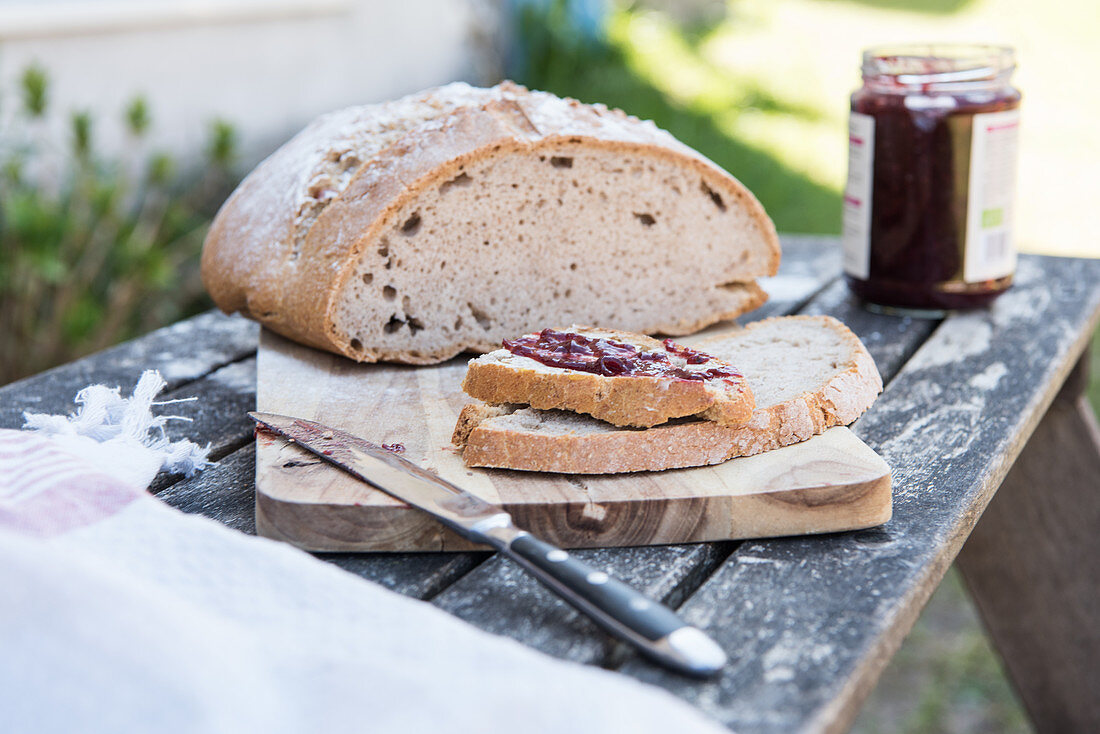 Sour dough bread with butter and jam on a table outside