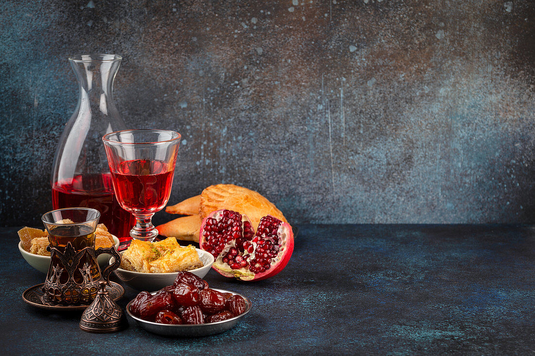 Ramadan kareem Iftar meal with dates, baklava, traditional Arabic sweets, fruit, Arab tea and rose sherbet beverage
