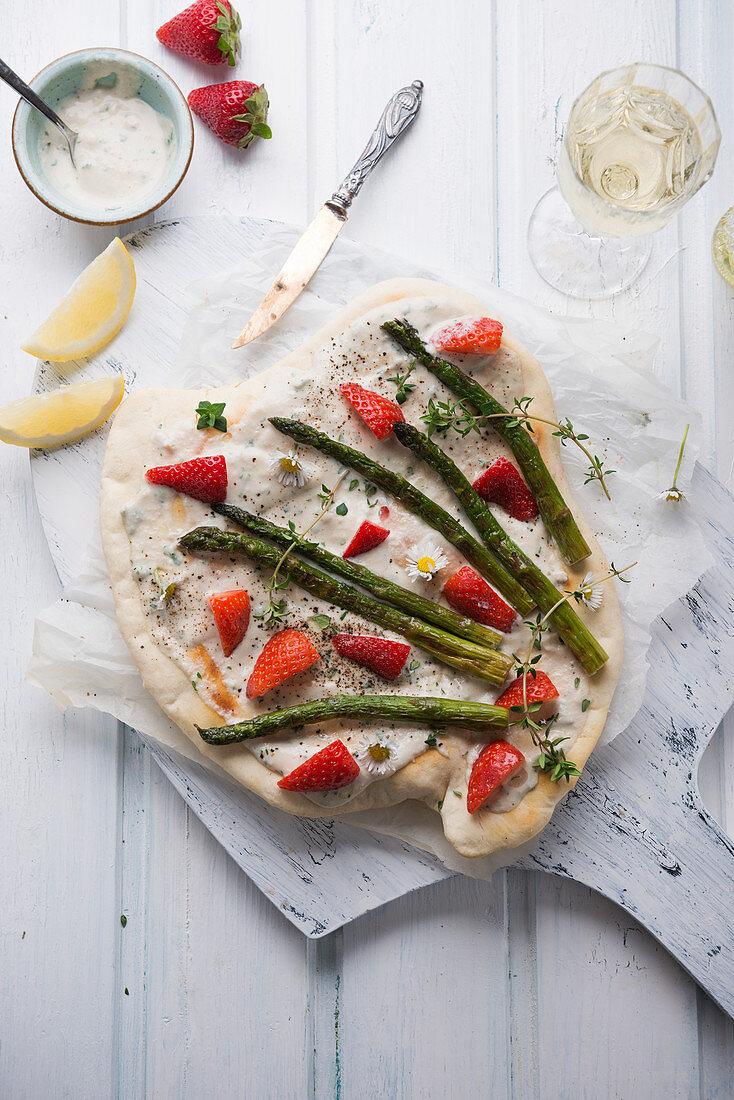 Vegan tarte flambé with cashew nut cream, green asparagus, strawberries and daisies