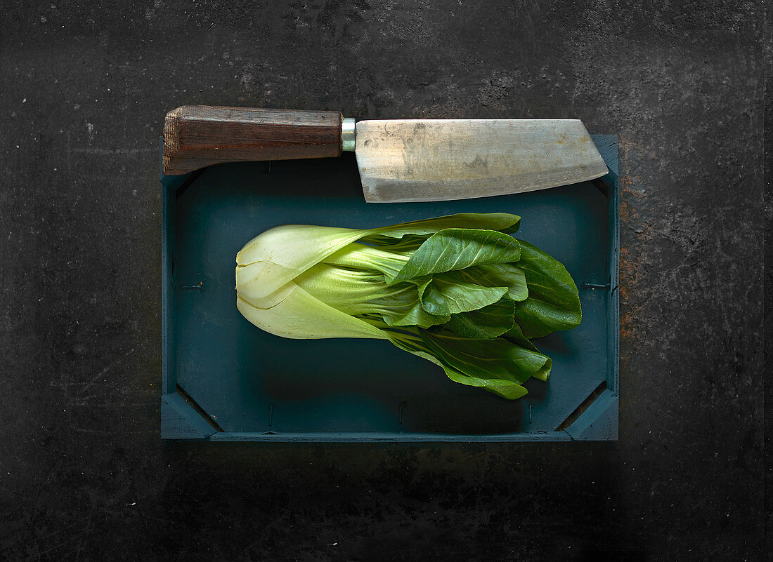 Bok choy in a wooden crate with a meat cleaver