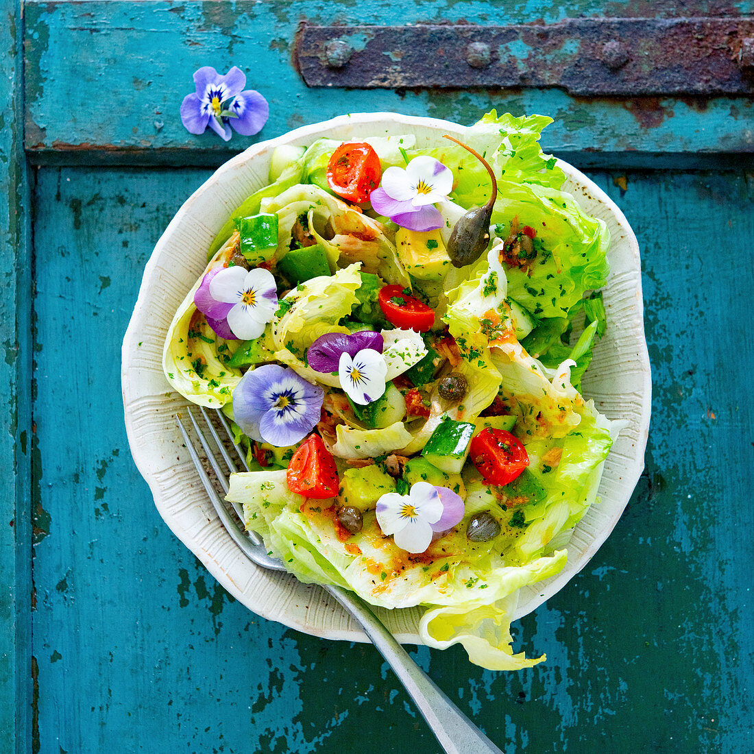A mixed leaf salad with tomatoes, capers and flowers