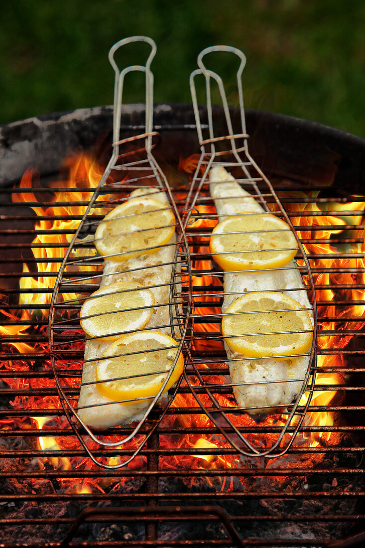 Zander fillets in fish baskets on a grill
