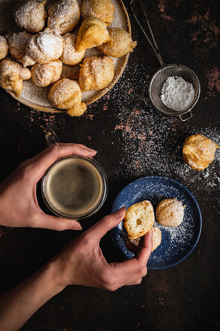 Mini donuts with powdered sugar and a cup of coffee