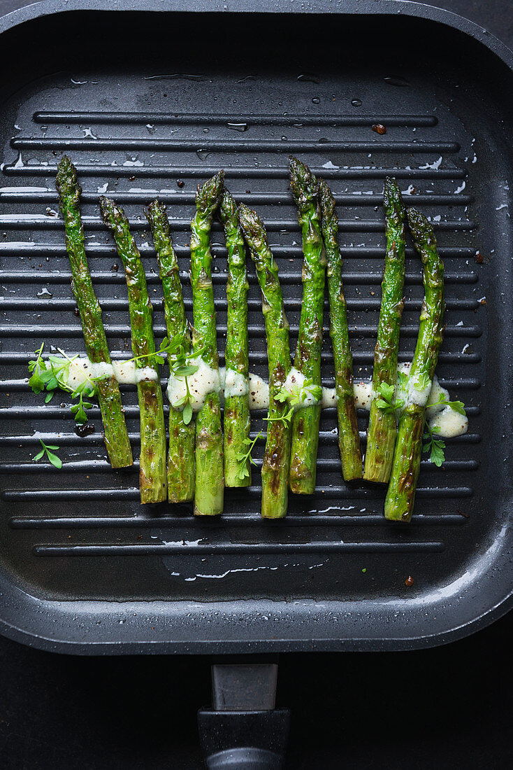 Green asparagus with vegan hollandaise and cress in a grill pan