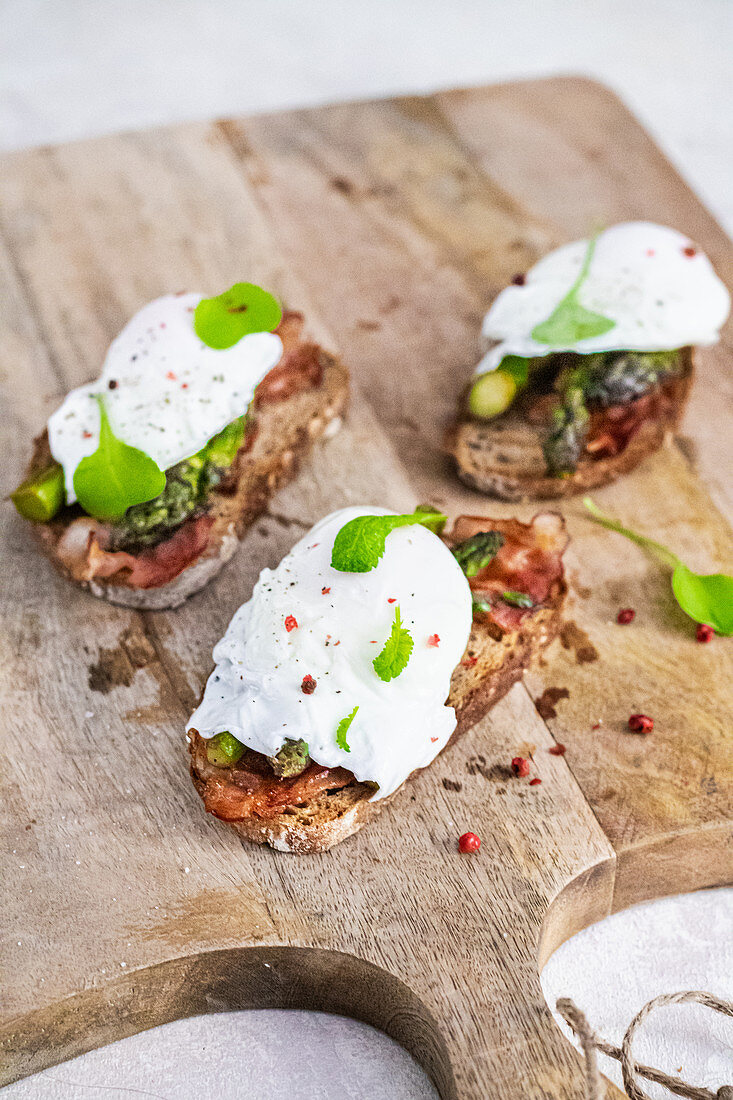 Toasts with green asparagus bacon and poached egg