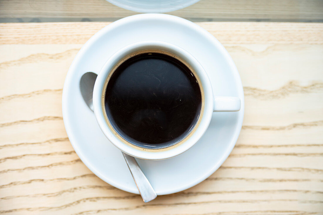 Cup of black filter coffee on wooden background