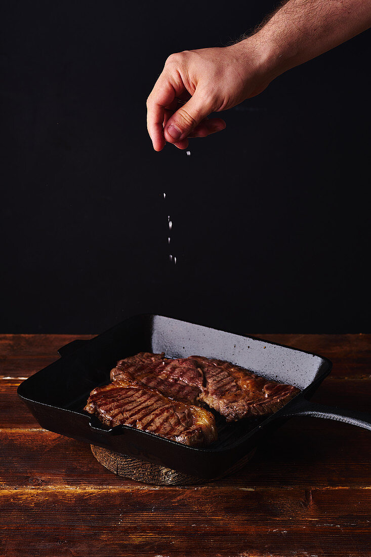 Male hands adding salt to beef steak on grill