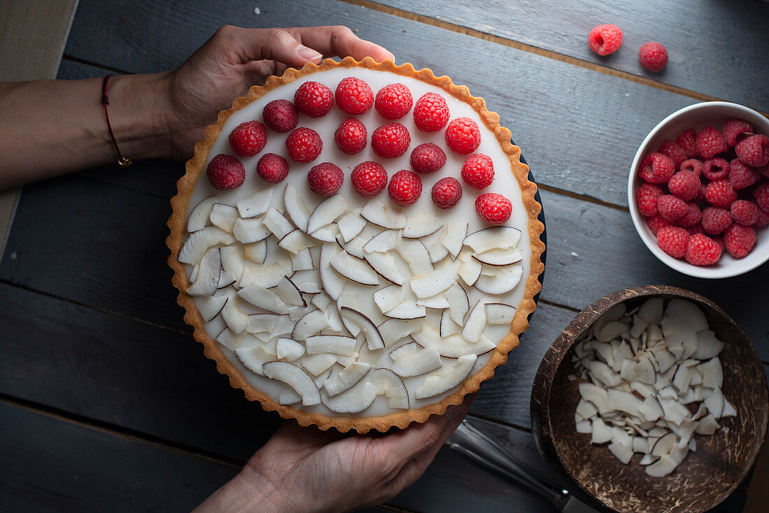 Coconut tart with coconut chips and raspberries