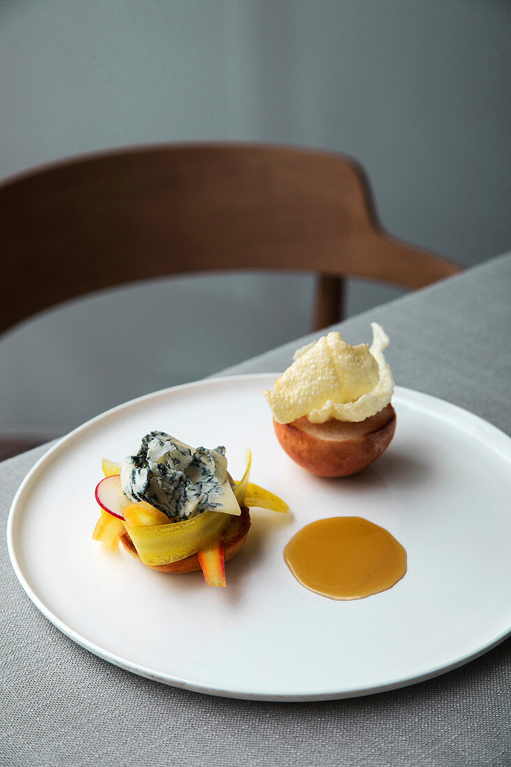 Milk rolls with gorgonzola, carrots, radishes, rice paper chips and sweet and sour sauce