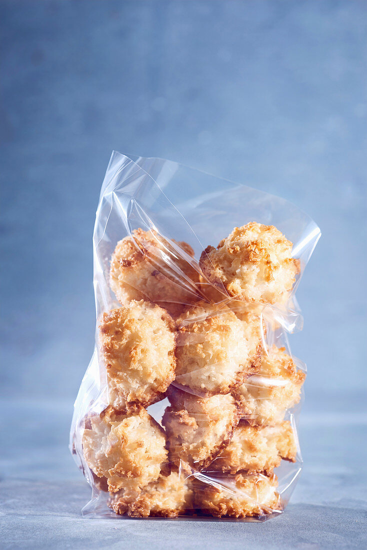 Coconut macaroons in a cellophane bag against a blue background