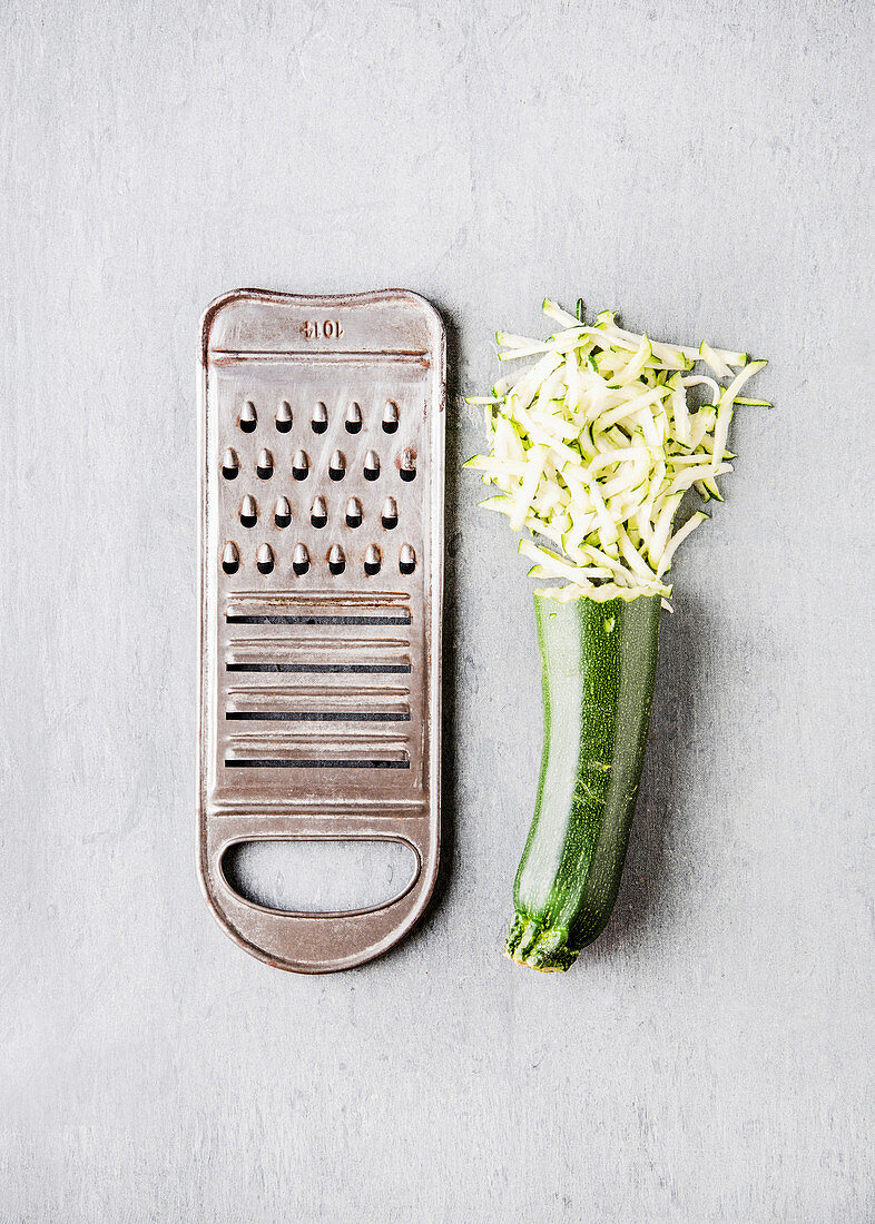 Zucchini, half grated, next to a vegetable grater