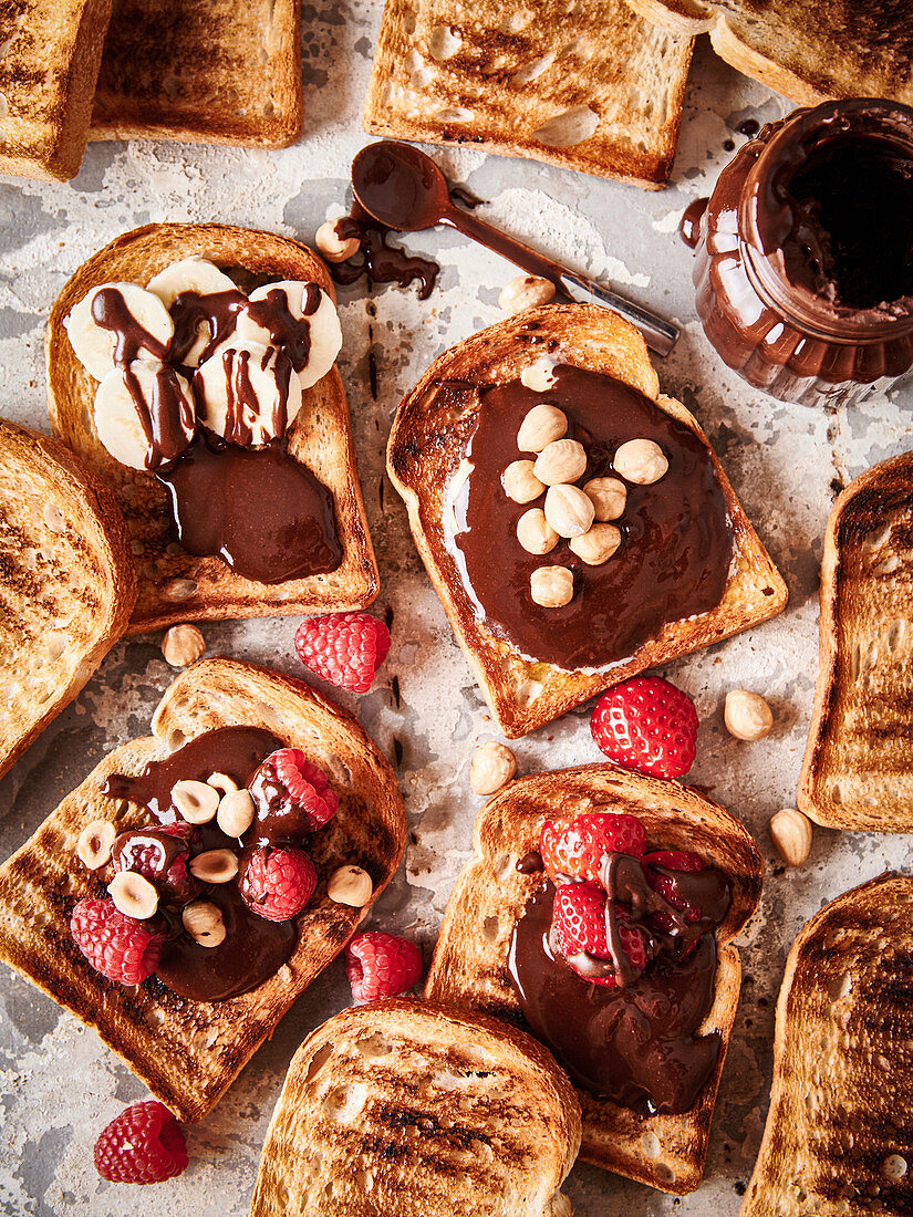 Several slices of toast with nut nougat cream and fruit