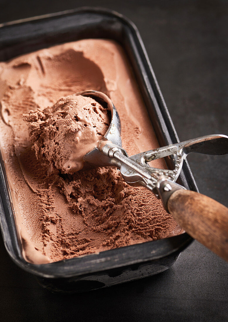 Chocolate ice cream in an ice cream container with an ice cream scoop