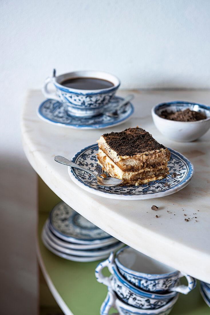 Tiramisu slice on a blue plate on marble with coffee