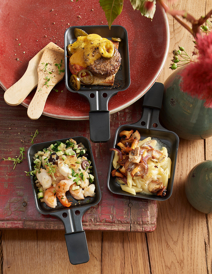 Raclette pans with seafood, a cheeseburger and pasta