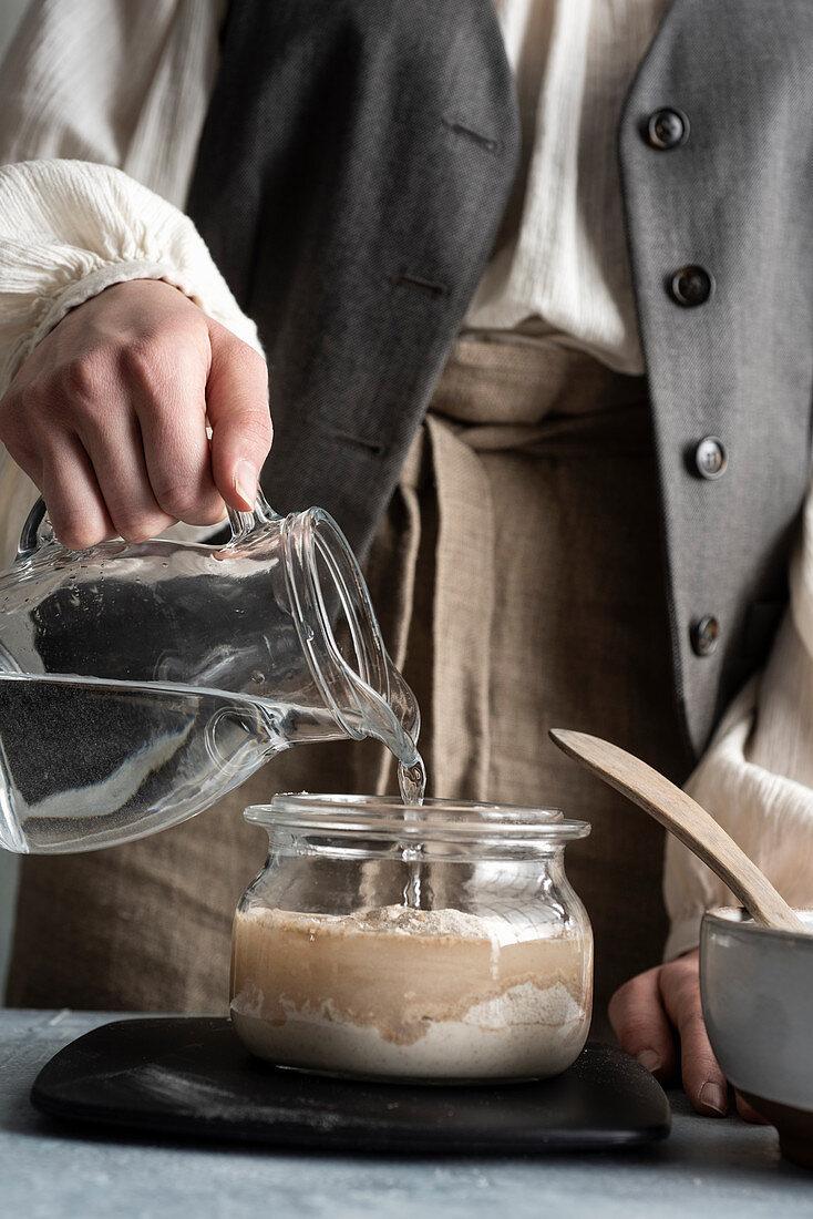 Pouring lukewarm water into a sourdough starter for Italian sourdough bread