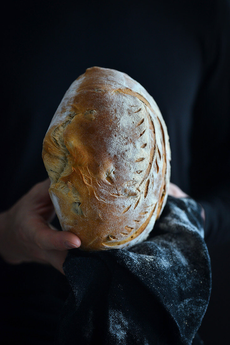 Man holding olive bread in his hands