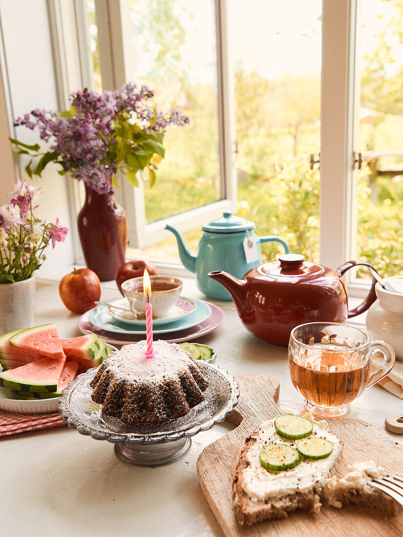 Teatime at the open window with bread, cake and fruit