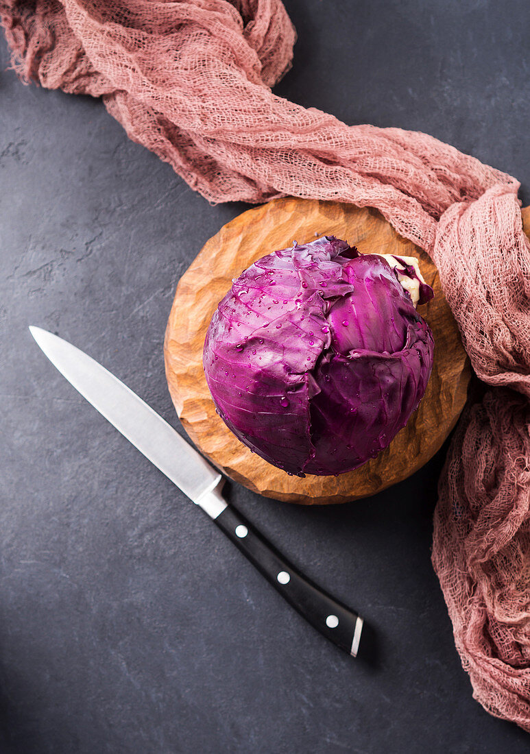 Red cabbage on wooden cutting board ready to be cut