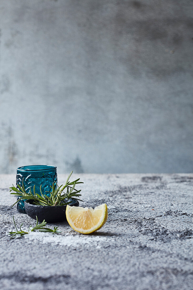 Still life with rosemary and a lemon wedge