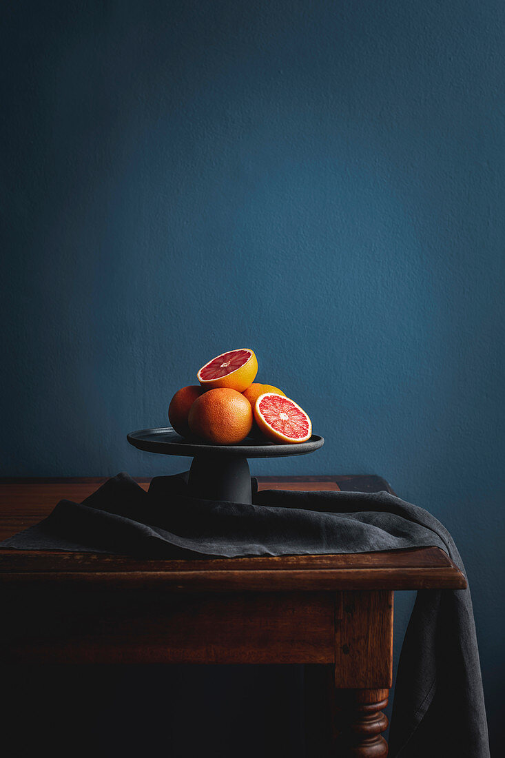 Pink grapefruit, whole and halved on a cake stand against a dark background