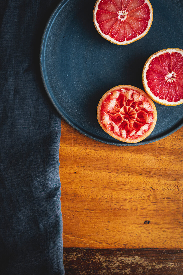 Pink grapefruit halves, one squeezed out