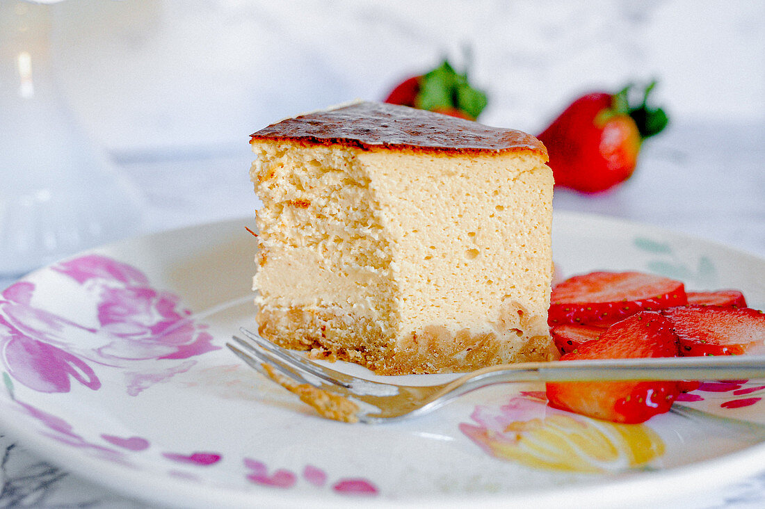 A piece of amarula cream cheese cake with strawberries
