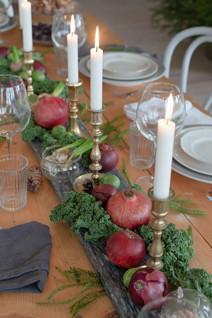 Centrepiece of candles, pomegranates and vegetables on set dining table