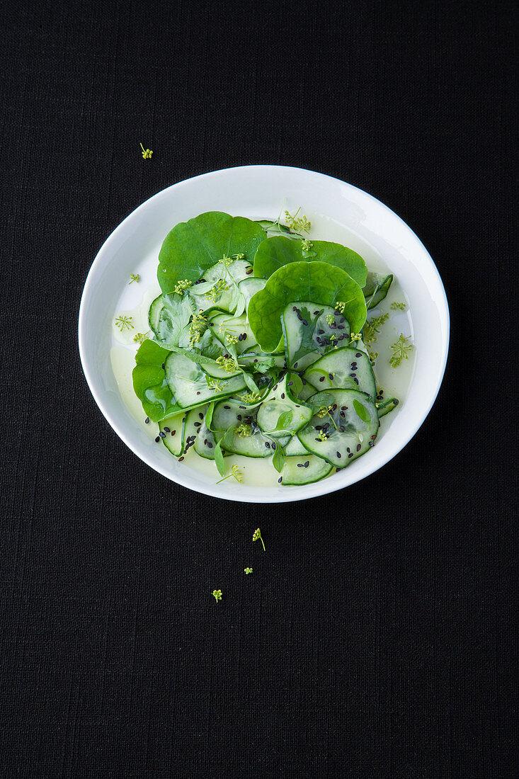 Cucumber salad with black sesame seeds, nasturtium and fennel flowers