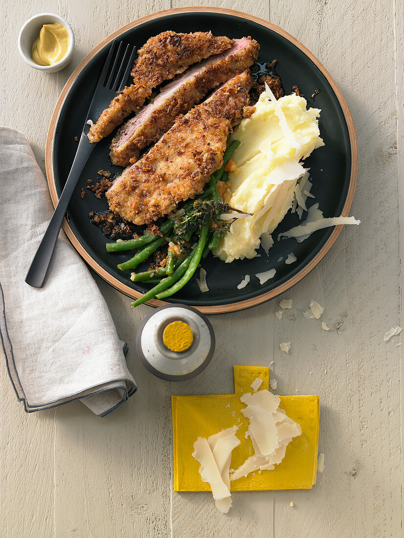 Pork neck schnitzel in roasted onion and panko crust with mashed potatoes and beans