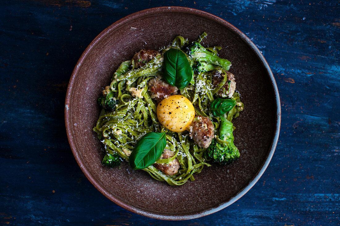 Tagliatelle with meatballs, pesto, broccoli and basil