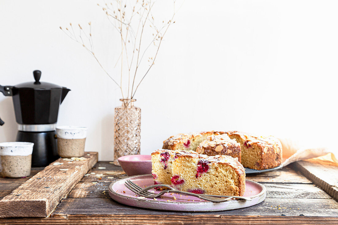 Ricotta cake with rasberries served on pink plate and wooden background.