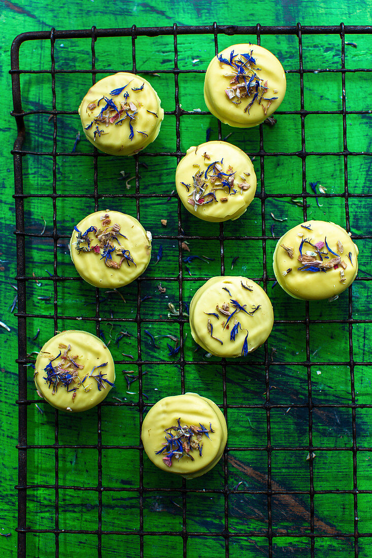 Cookies with a glaze and edible flowers on a cooling rack