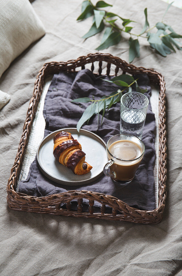 Wicker tray with coffee and croissant on a linen bed. Breakfast in bed.