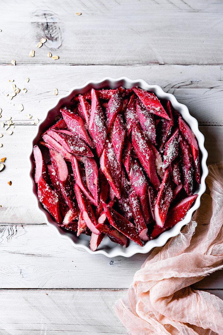 Cut rhubarb sprinkled with sugar in a baking dish.