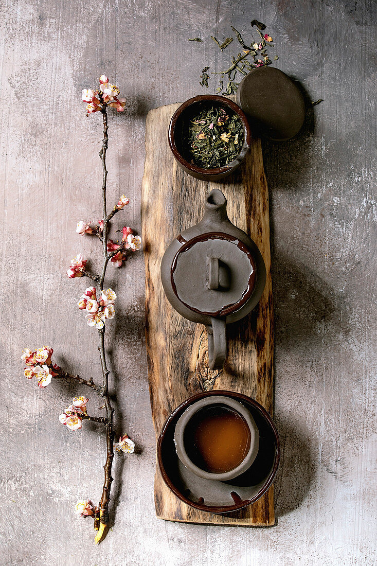 Tea drinking wabi sabi japanese style dark clay cup and teapot on wooden board with blooming cherry branches. Grey texture concrete background. Flat lay, space