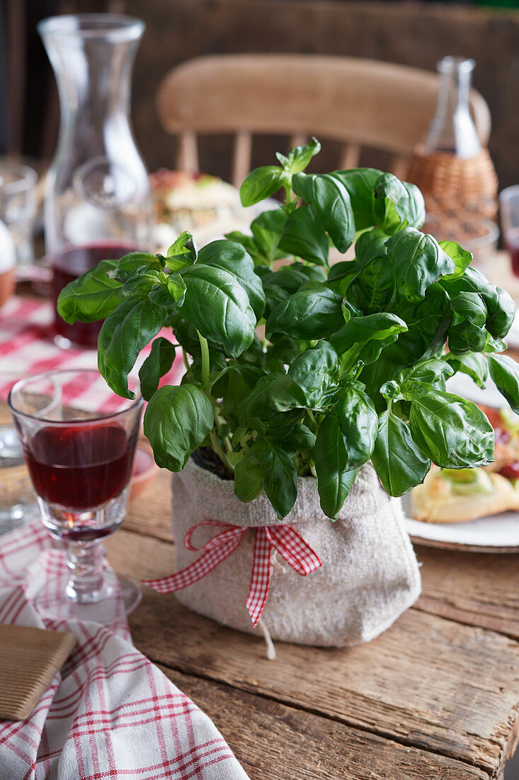 Basil in a jute sack on a wooden table