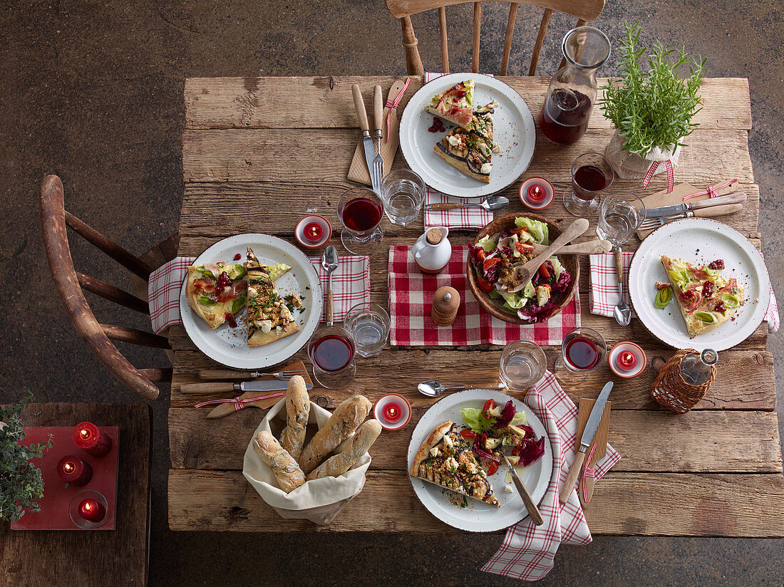 A table laid with pizza, salad and red wine