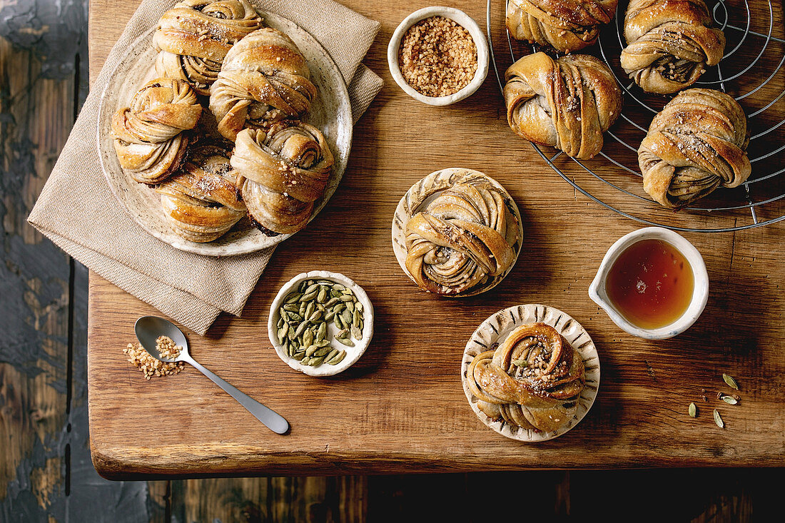 Traditional Swedish cardamom sweet buns Kanelbulle in plate, ingredients in ceramic bowl above on wooden table. Flat lay, space