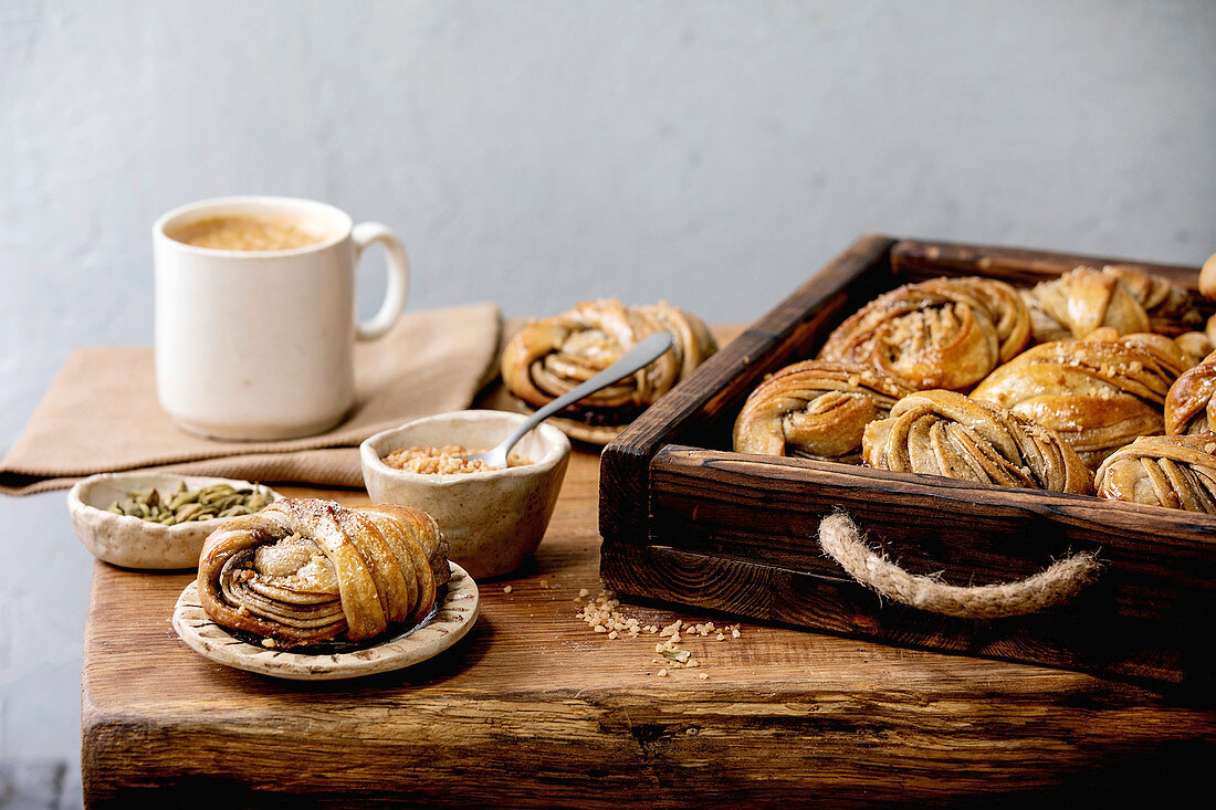 Traditional Swedish cardamom sweet buns Kanelbulle in wooden tray, cup of coffee, ingredients in ceramic bowl above on wooden table.
