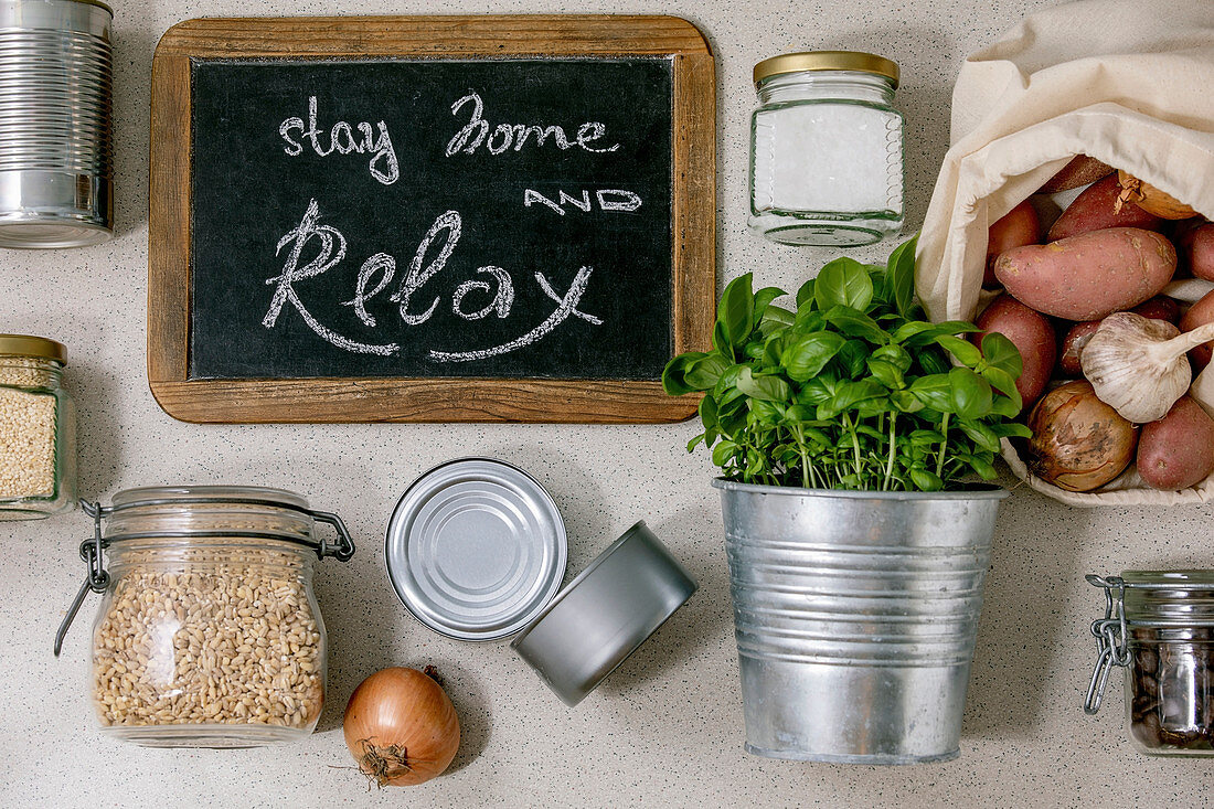 Flat lay of food supplies crisis for quarantine isolation period. Different glass jars with grains, cans of canned food, vegetables, chalkboard handwritten lettering Stay home and relax.
