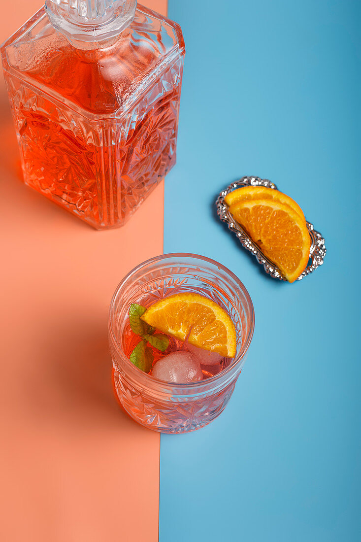 From above of glass of fresh cold cocktail with ice cubes and mint placed on colorful background with slices of ripe orange