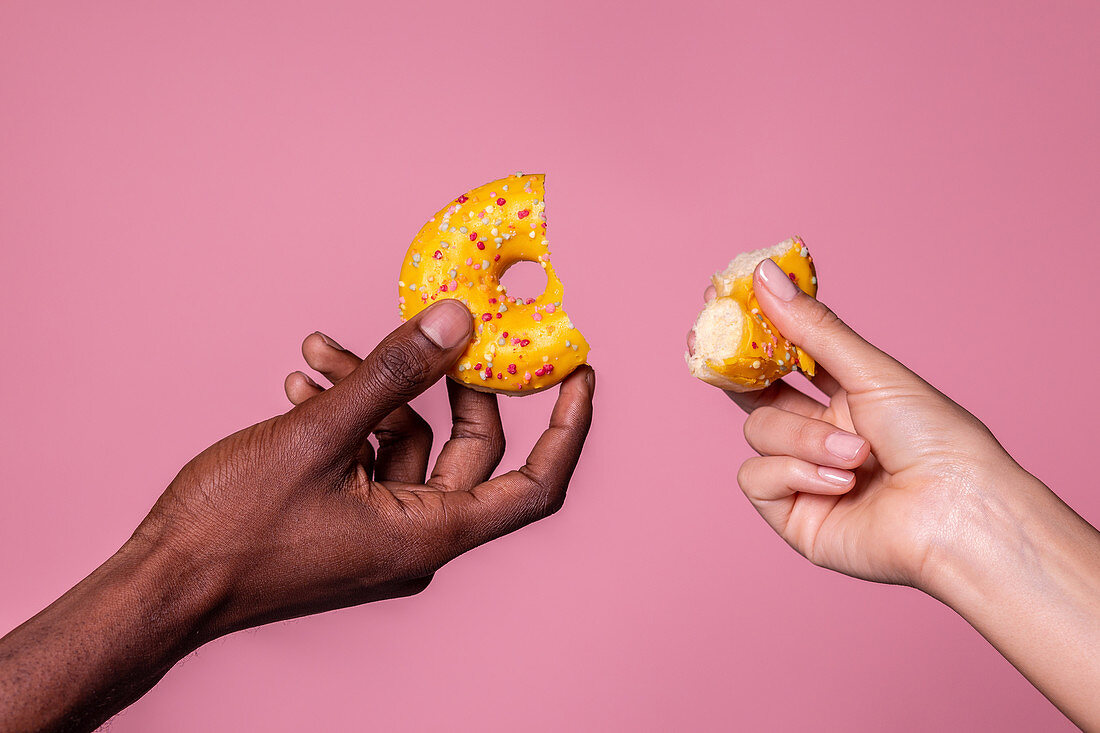 Crop hands of anonymous multiracial couple holding sweet bitten doughnuts on pink background