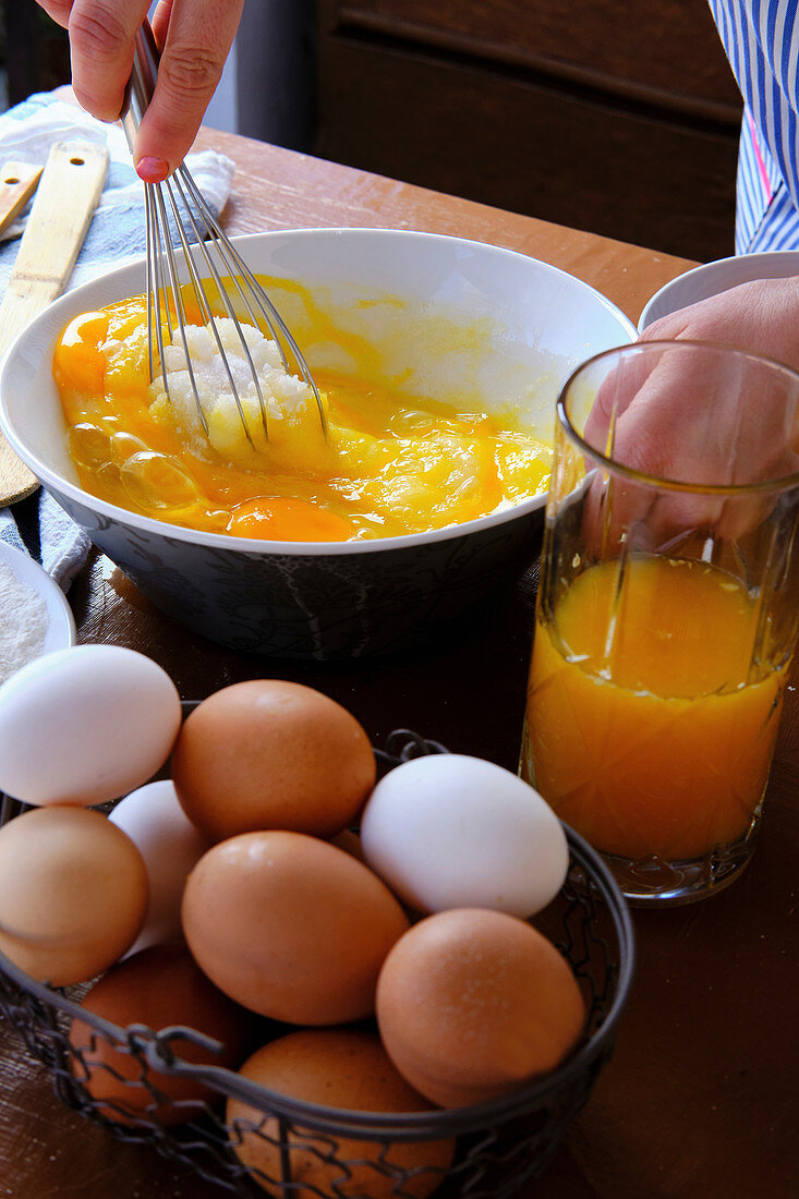From above crop female using whisk to mix sugar with raw eggs near cup of citrus juice while cooking pastry on kitchen table